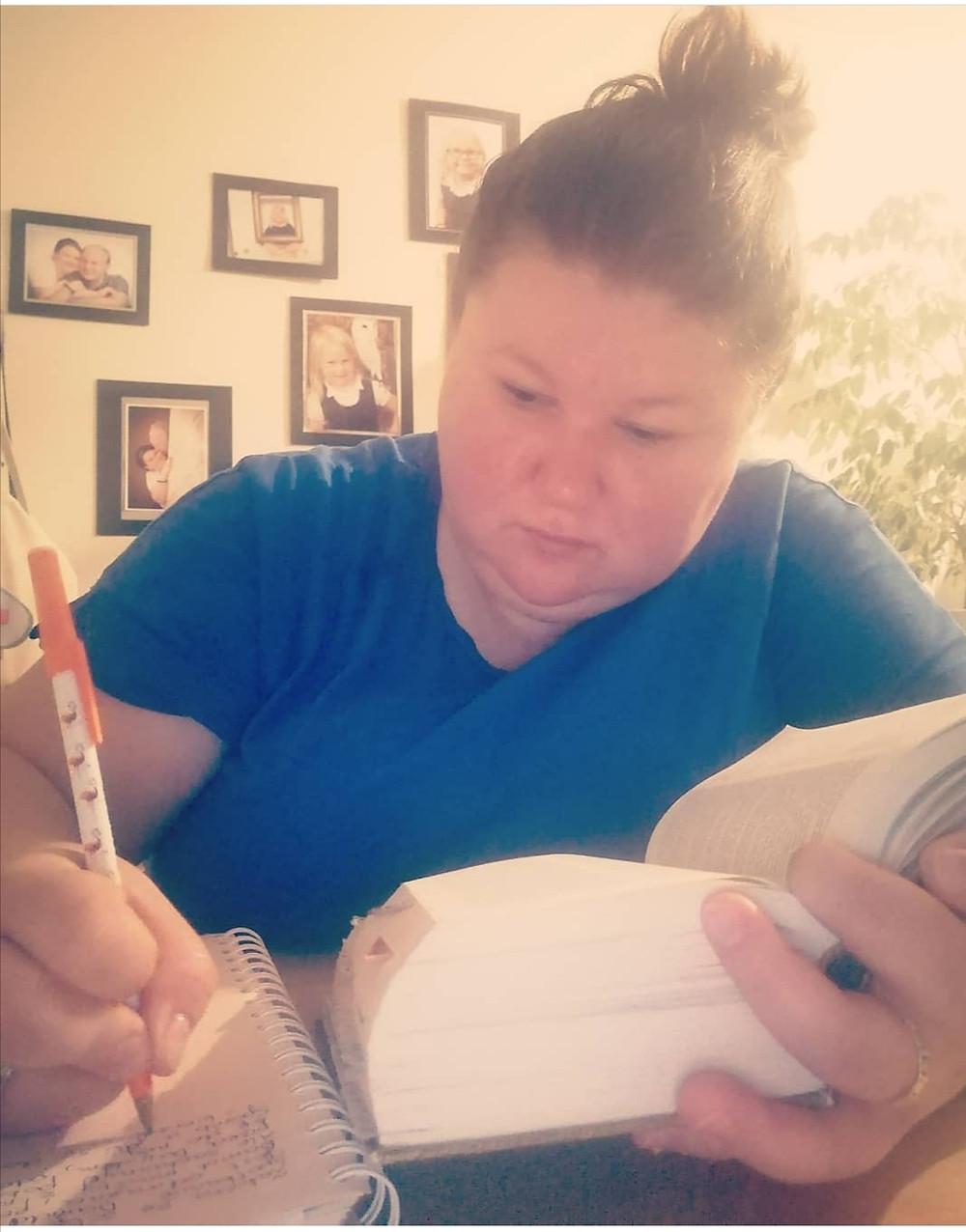 kobieta czytająca Pismo święta i notująca swoje przemyślenia