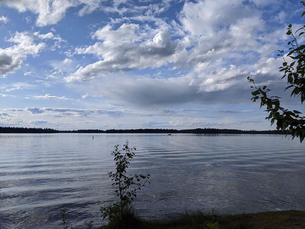 Slight ripples on a large lake. The water looks fresh and clear, and the sky is a beautiful mix of puffy clouds and bright blue sky. The dark shoreline cuts across the middle horizon of the image.
