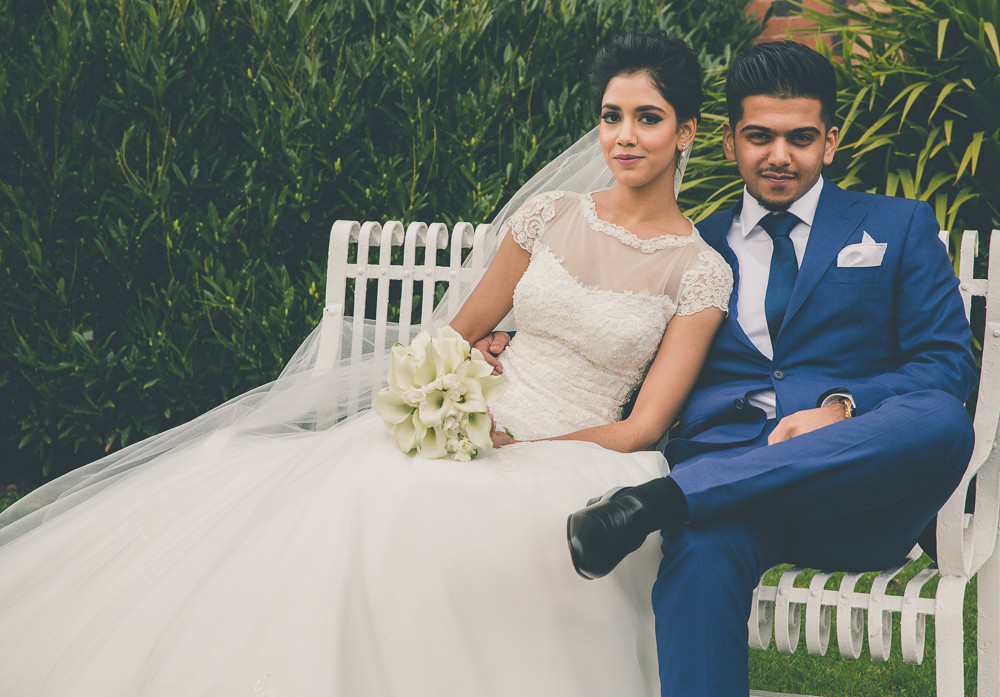 Groom and bride sit on bench