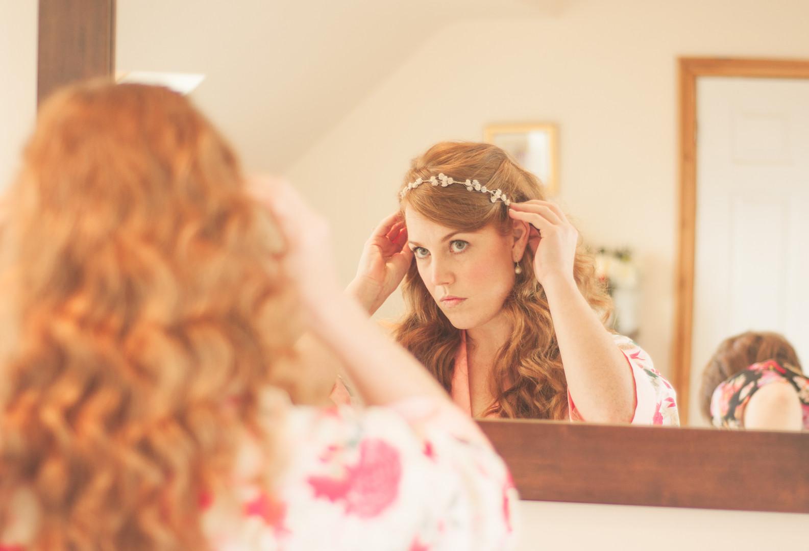 Bride fixes hair in mirror