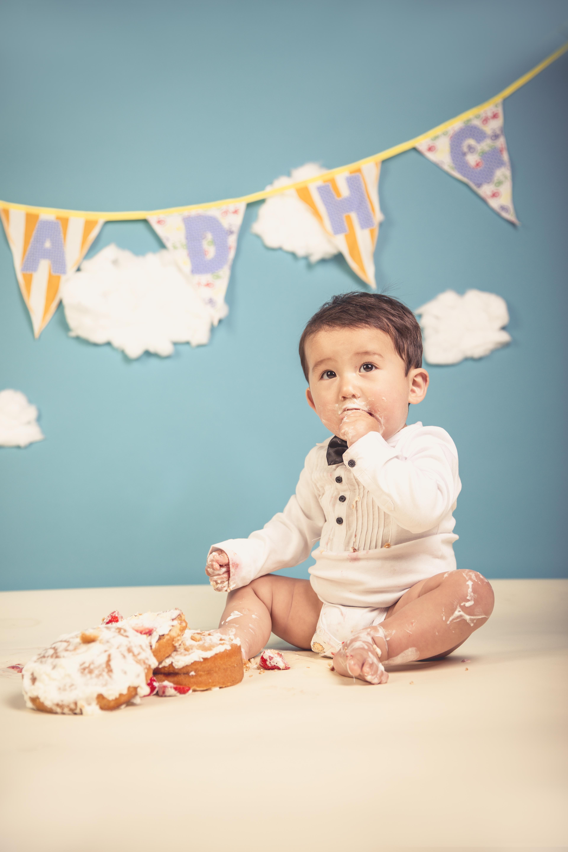 Baby in tuxedo eating cake.