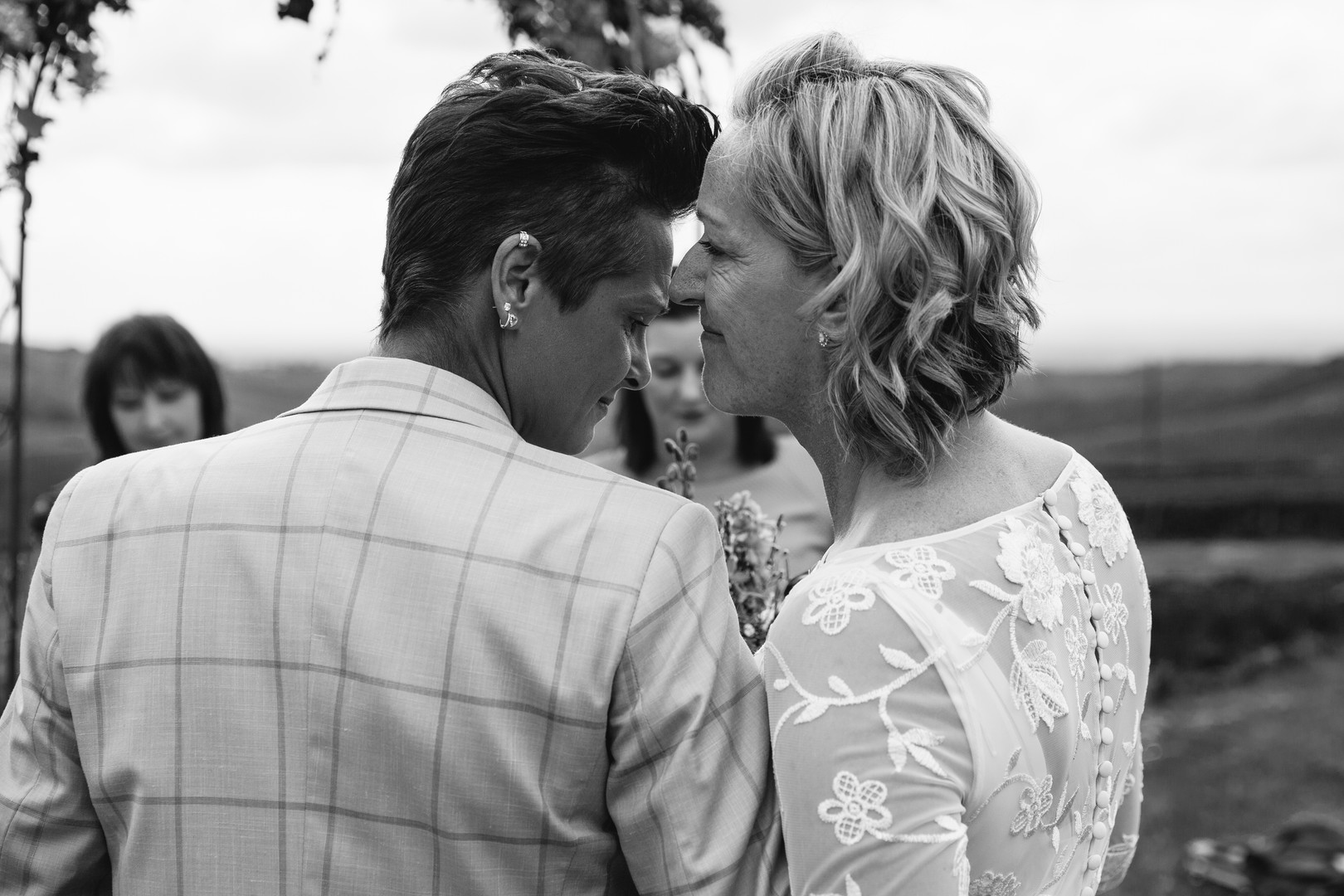 Black and white image during ceremony couple lean heads together