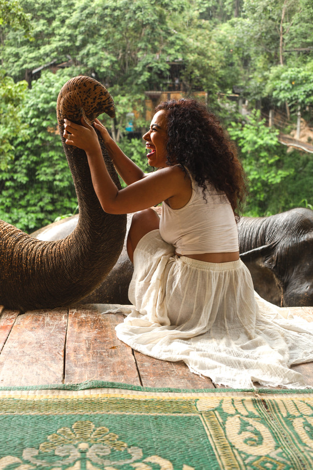 Woman wearing white plays with elephant