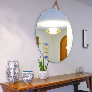 Modern round mirror hangs above cloisonne pots and plants