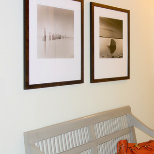 Black and white framed photographs paired above a front hall bench