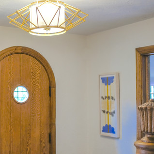 Artwork, in csutom white-whashed maple, talks with a modern brass light fitting in the tudor style front hall