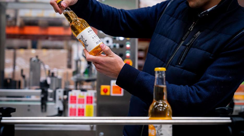 Une personne tenant une bouteille de cidre dans sa main