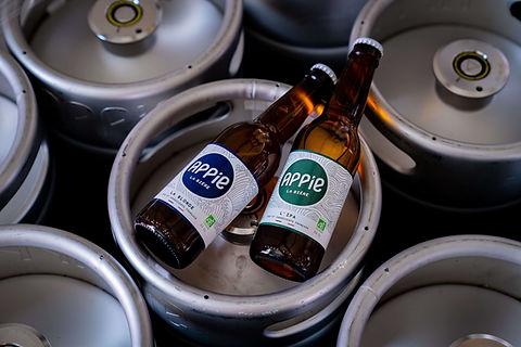 deux bouteilles de bière posées sur un fût de bière
