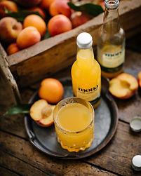 une bouteille de craft soda posée sur un plateau avec un verre, à côté d'un bac en bois rempli de pêches et d'abricots