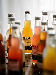 plusieurs bouteilles de craft soda posées sur une table en bois