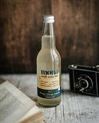 une bouteille de craft soda au citron posée sur une table avec un livre