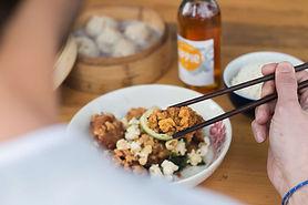 une personne mangeant un plat avec une bouteille de cidre en arrière-plan