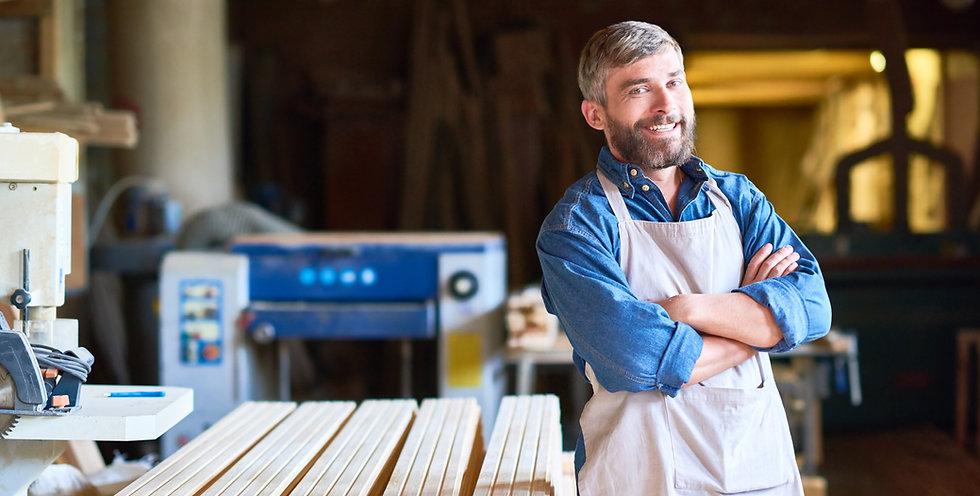 successful-carpenter-posing-in-workshop-