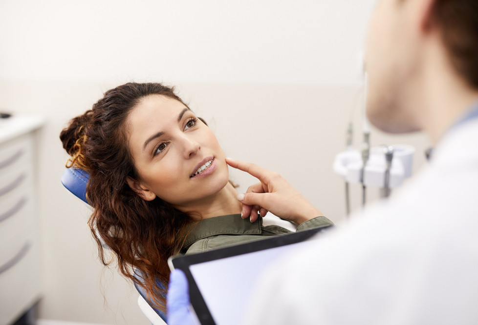 young-woman-consulting-dentist-NY5GS62_e