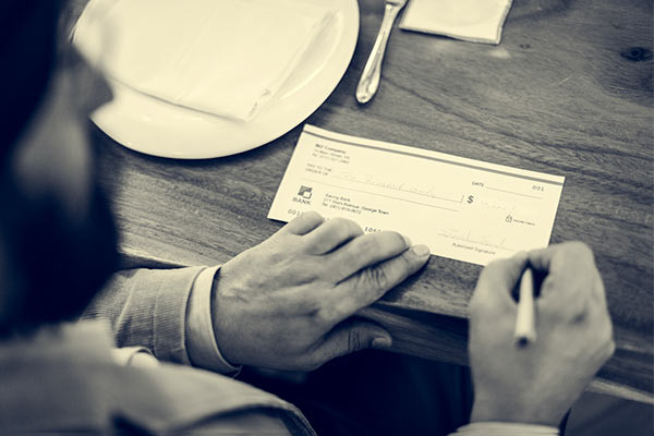 alimony deductions in florida image showing check being signed