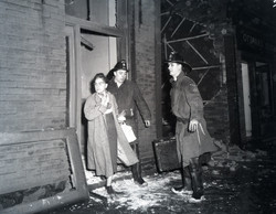 1958-10-25 Firefighters helping woman leave explosion site