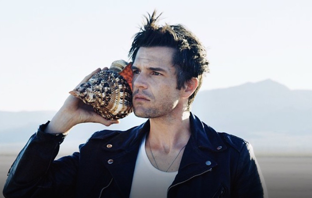 Brandon Flowers holding a seashell to his ear