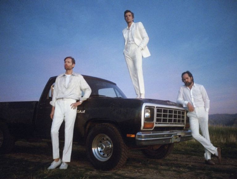 The Killers dressed in all white, posing with a black truck