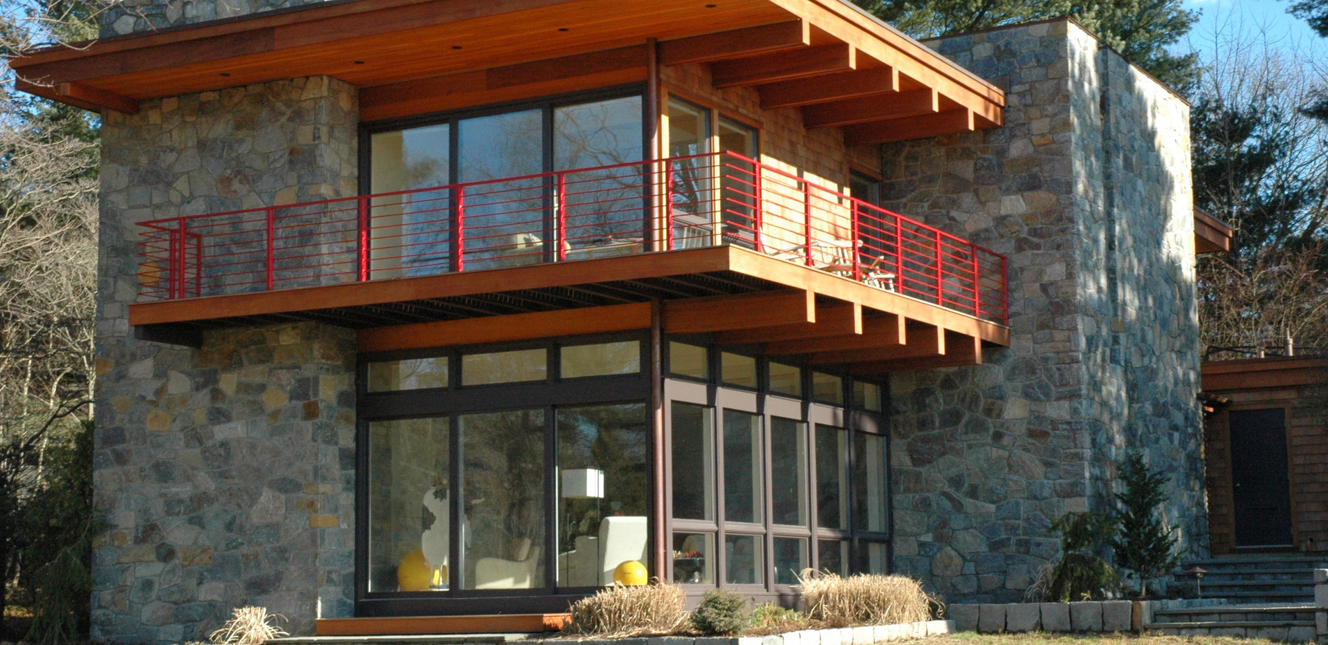 New Mahogany clad Facia, Soffit, Beams and roof overhang.  Spruce Mountain Stone Veneer.