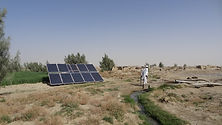 Two men walking by solar panels and stre