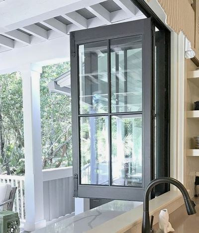 Picture of a bi fold window open and pushed back.
