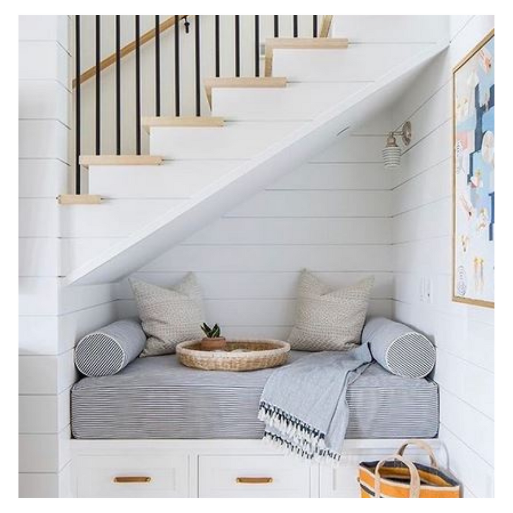 Seating arrangement under the stairs to create a reading space with a comfy seat and good lighting.
