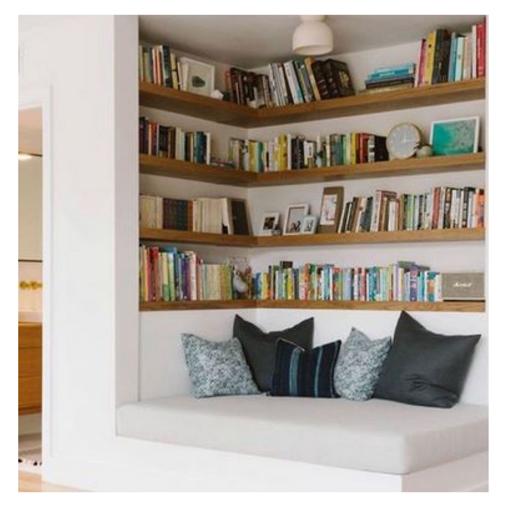 Corner of a room space set up as a reading nook with comfy seating, cushions and book shelves.