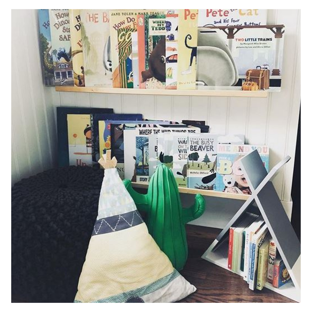 Childs reading nook with easy reach shelves and soft comfy seating