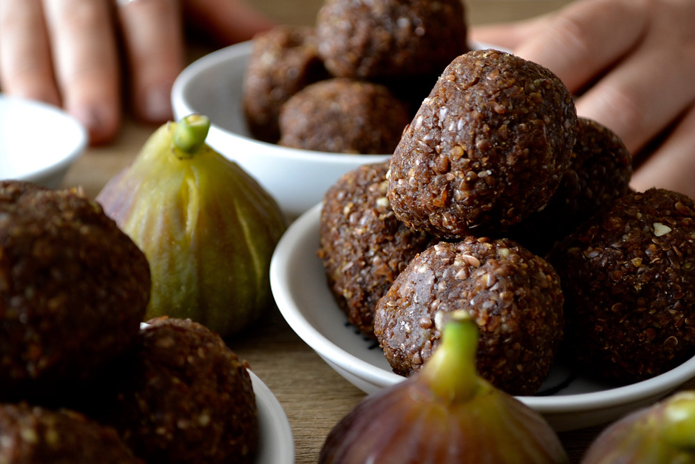 Bowl of linseed and fig bliss balls with fresh figs surrounding