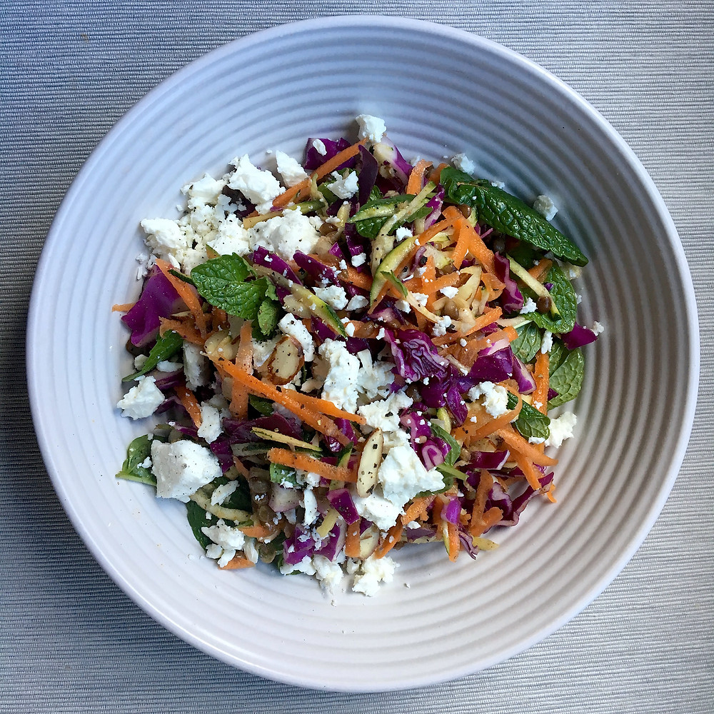 A bowl of fresh salad with lentil. almond and goats feta