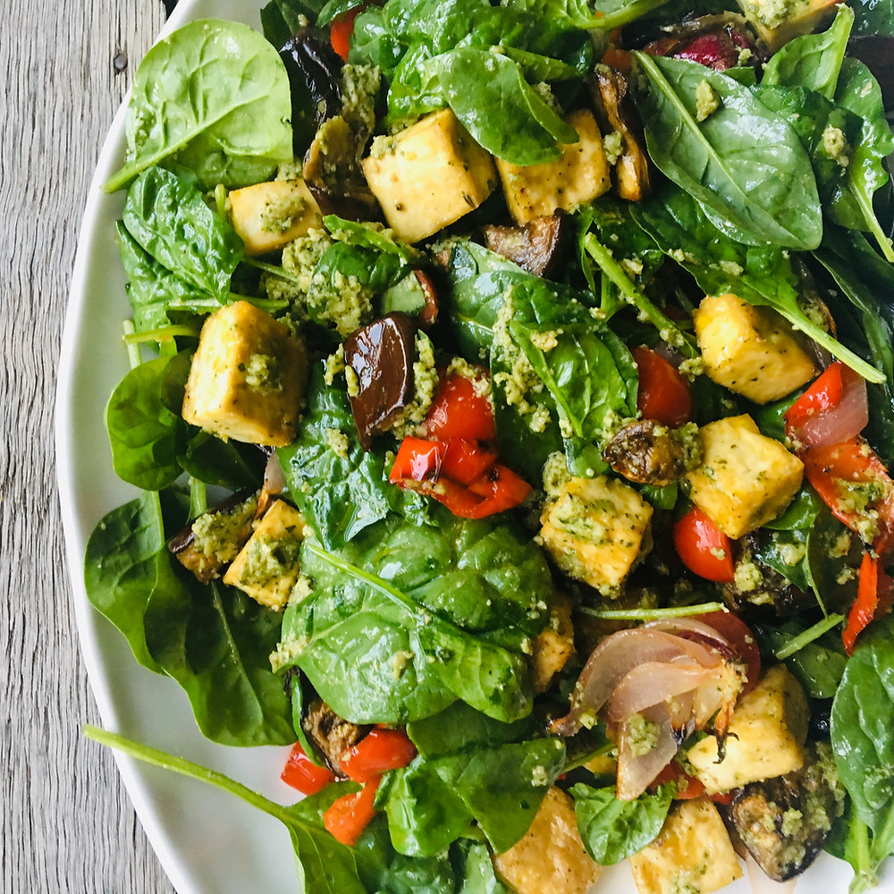 Warm mediterranean salad with spinach leaves, eggplant, tofu, tomato and capsicum