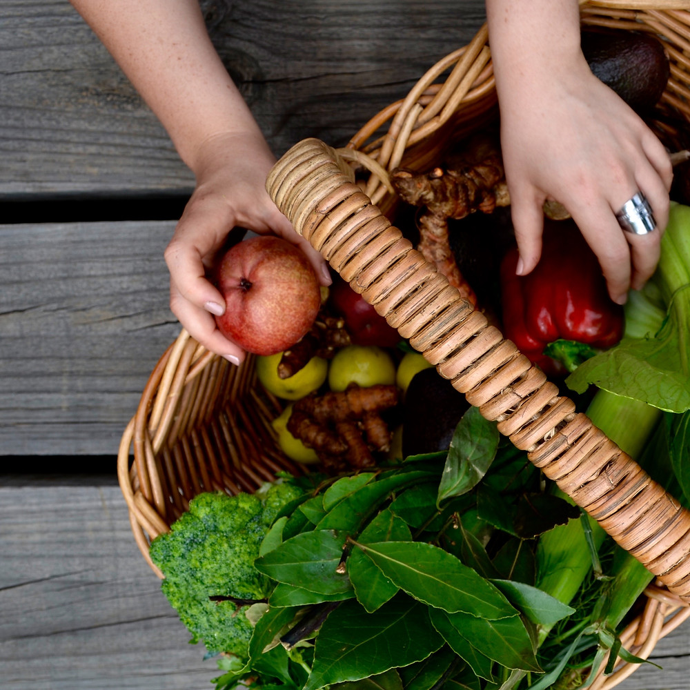 Wooden basket of fresh organic fruit and vegetables with hand reaching into it.