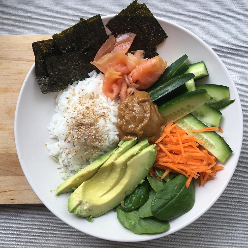 Birdseye view of sushi bowl / poke bowl. Featuring avocado, salmon, nori sheet,s rice and fresh vegetables.