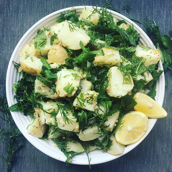 Bowl of potato salad with herbs and fresh lemon