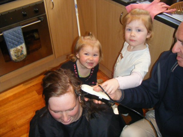 Kate with her father and two daughters as they shave her hair after cancer treatment.