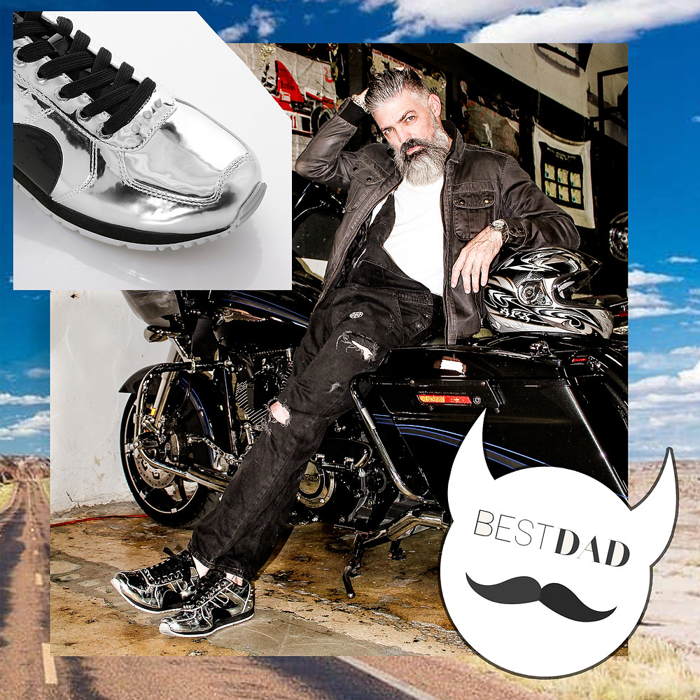 Dad wears Boston runner sneakers with black laces and silver finish and poses with a motorcycle in in ripped, distressed jeans and a black jacket.