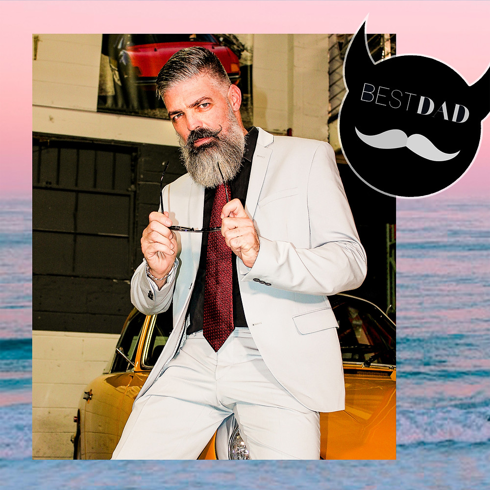 Dad with beard wears sunglasses with formal grey suit and tie against beach sunset.