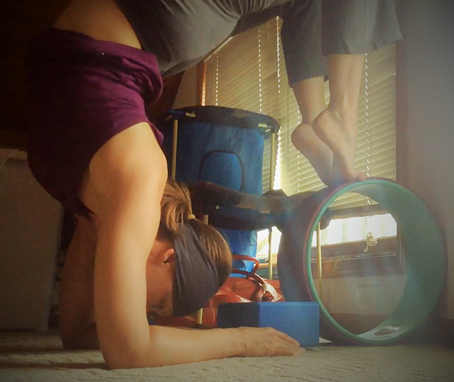 A low quality picture of me working on a Scorpion pose with a Yoga block and my Plexus Yoga Wheel