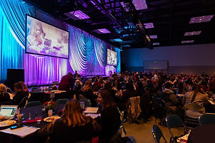 ICFW General Session room with attendees at tables, blue overlay