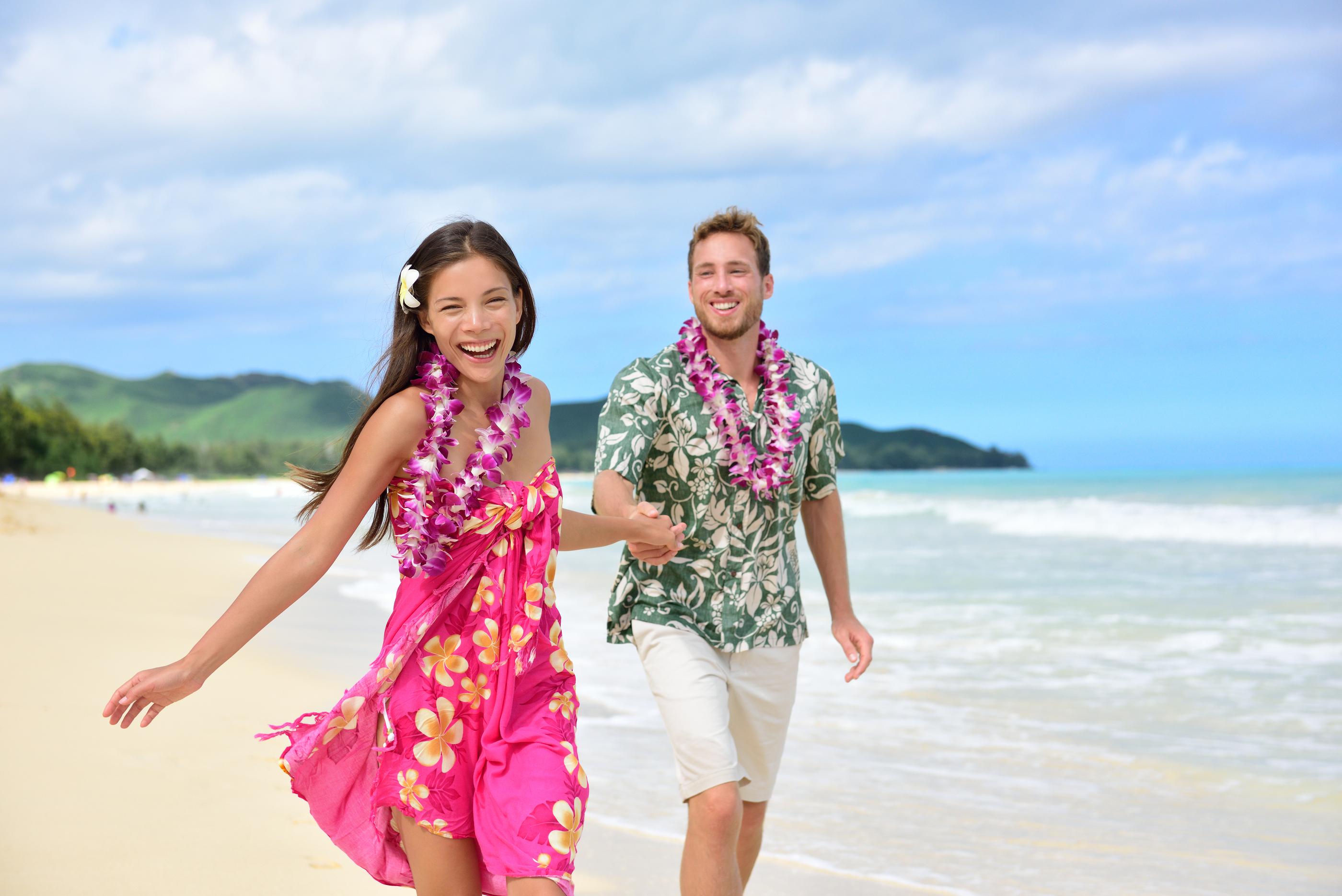 Happy couple having fun running on Hawaii beach vacations in Hawaiian clothing wearing Aloha shirt a