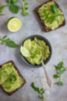 rye toasts with guacamole and arugula on