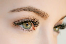 Close up view of beautiful green female eye with long eyelashes, smooth healthy skin. Eyel