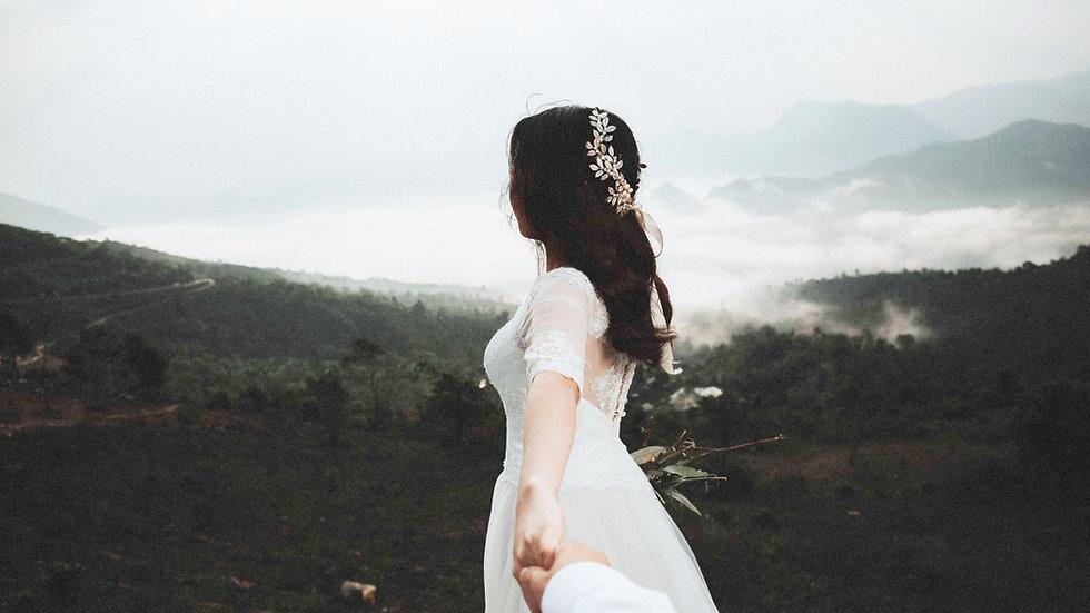 Bride in wedding dress holding fiance's hand