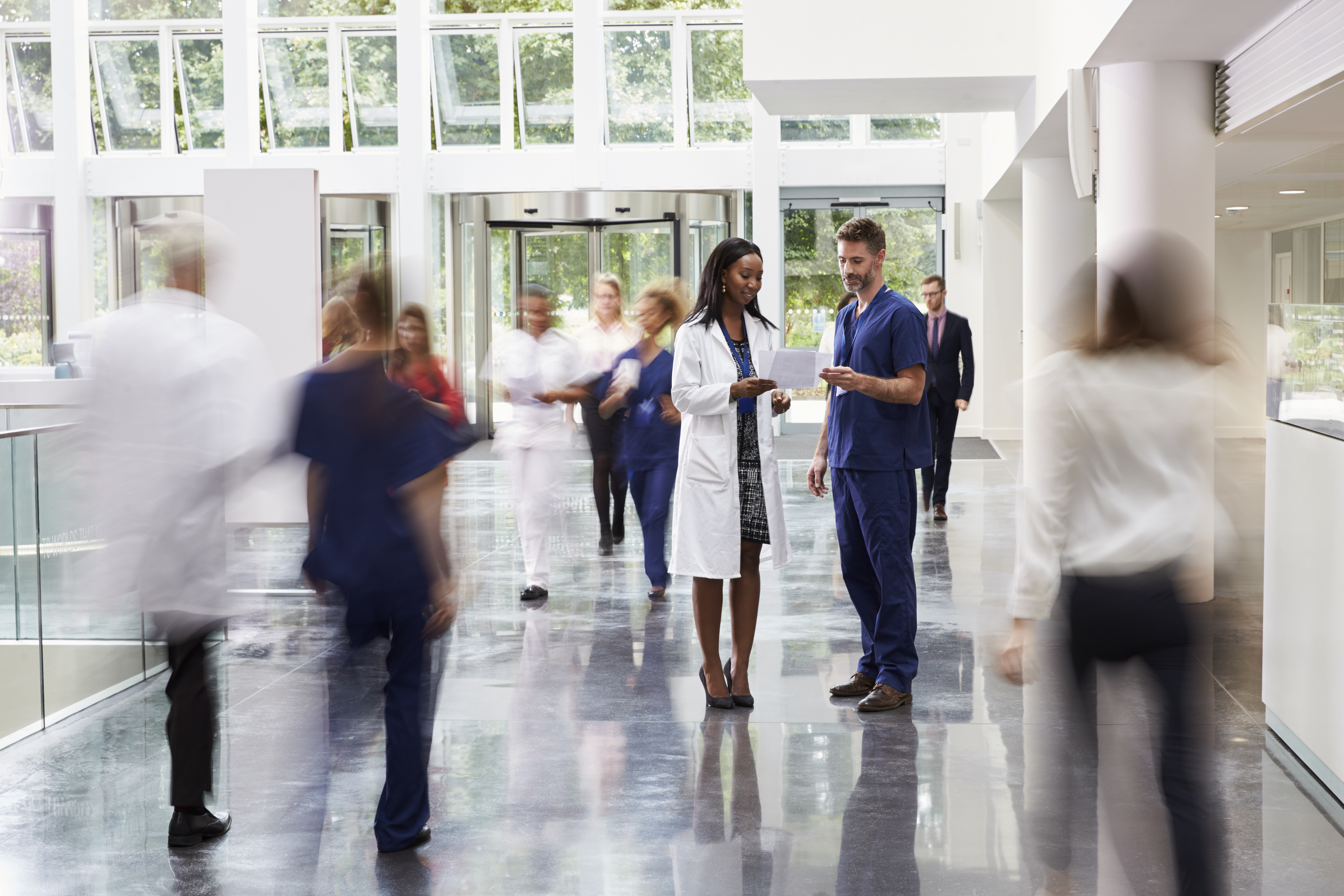 Staff In Busy Lobby Area Of Modern Hospital