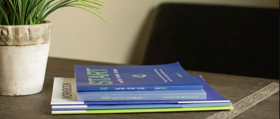 START Books on Desk Image.png