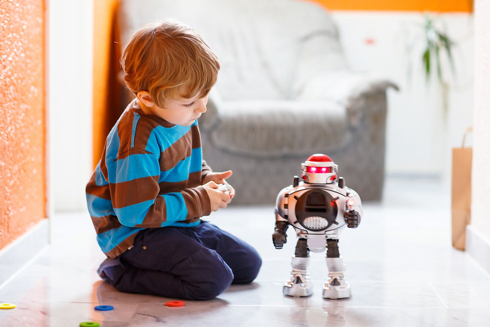 Little blond boy playing with robot toy