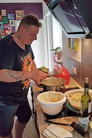 Ben steht in der Küche am Herd und macht Spätzle
