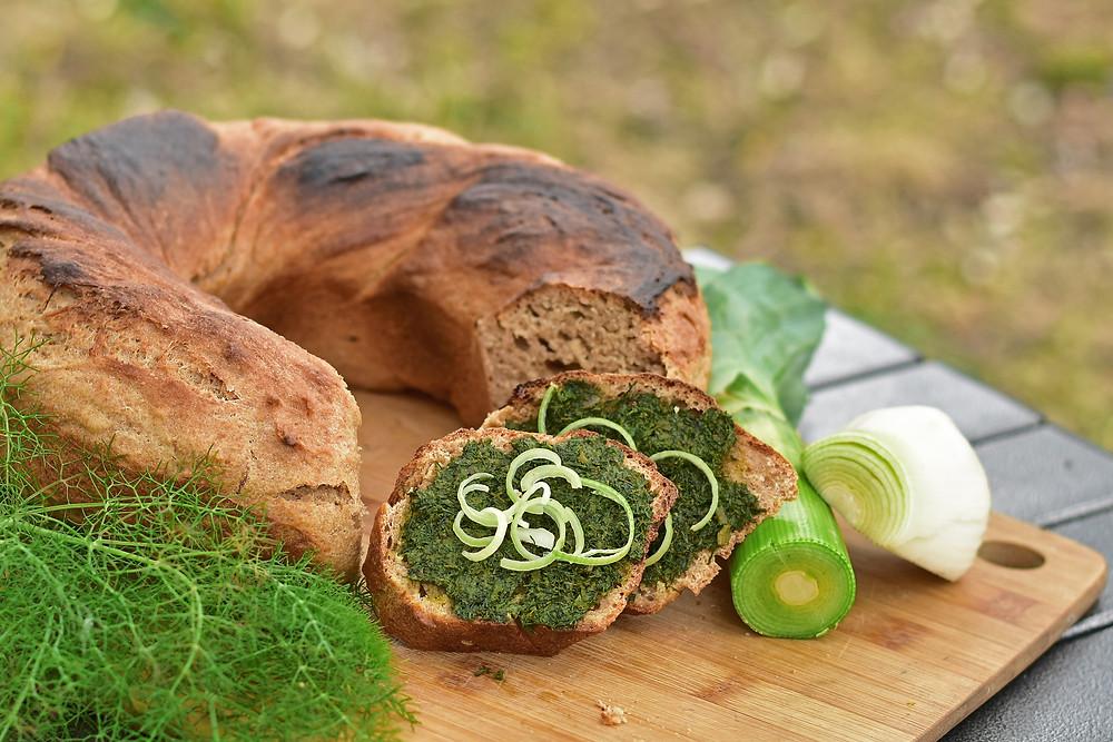 Vollkornbrot aus dem Campingbackofen Omnia auf einem Holzbrett serviert mit selbstgemachtem Fenchel-Aufstrich.