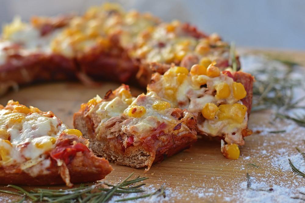 Pizza aus dem Campingbackofen Omnia auf einem Holzbrett serviert.