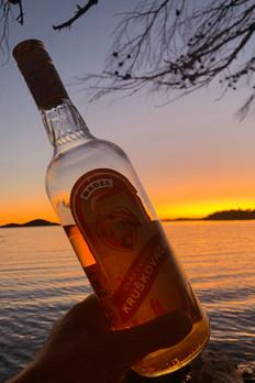 Flasche Kruskovac in Kroatien beim Sonnenuntergang am Meer